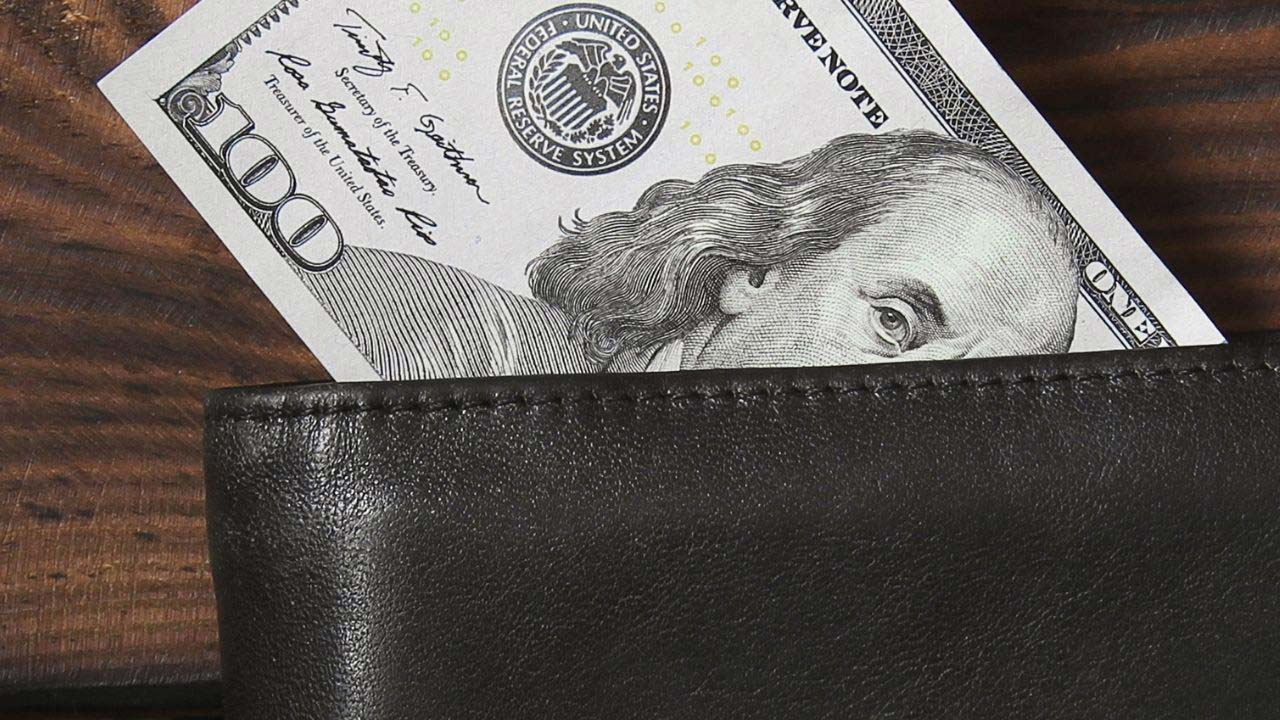 $100 bill sticking out of a wallet