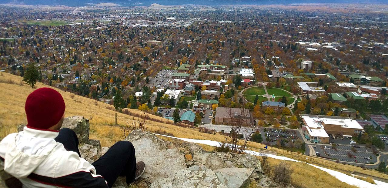 Student sitting on a hill  overlooking school campus