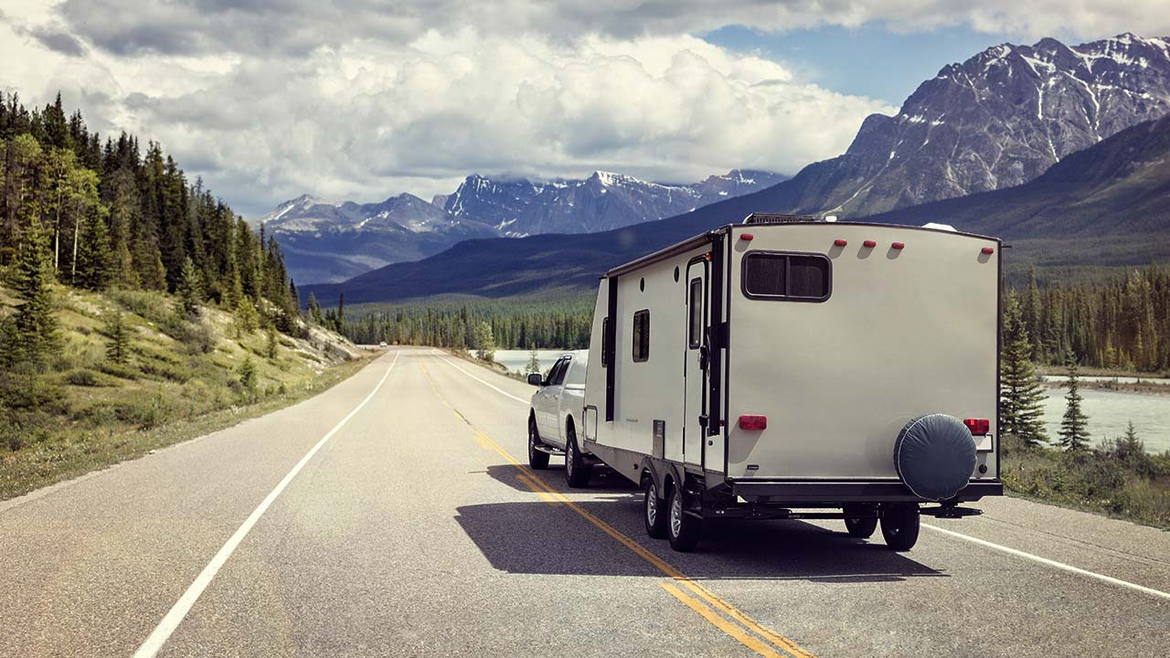 Pickup truck with camper on open road